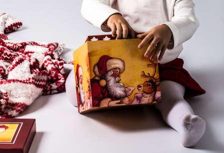 children s feet: child opening Christmas gift Stock Photo