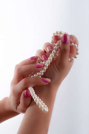cultured pearls presented with nails painted pink photo