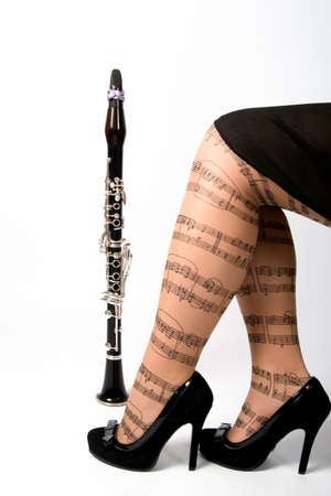 clarinete: Pies de niña y clarinete en el fondo blanco