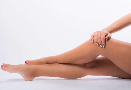 pies sexis: uñas decoradas con colores neutros y las piernas Foto de archivo