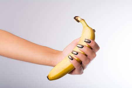 hand with painted nails clutching a banana 写真素材