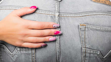 woman's hand with painted nails and texture of jeans