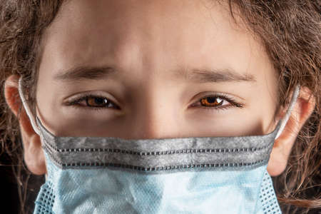 sad little girl with surgical mask to protect herself and protect from covid-19