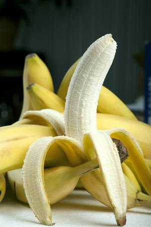 peeled banana: Peeled banana isolated in front of a few  bananas Stock Photo