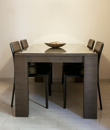 dining table and chairs: Modern dining room with brown chairs and a table with glass coating