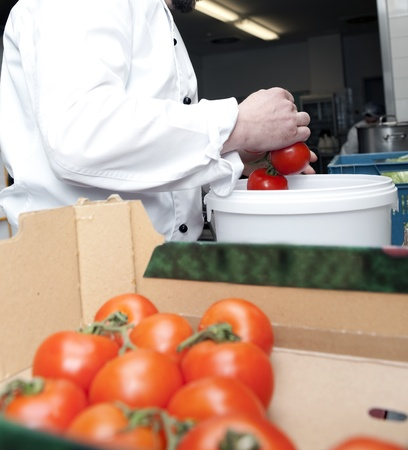 cook selects tomatoes from a box in the kitchen of a restaurant