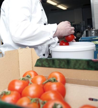 selects: cuoco seleziona i pomodori da una casella nella cucina di un ristorante Archivio Fotografico