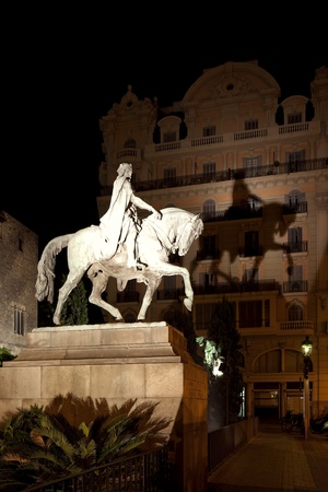 nightscene: Nightscene of an illuminated stone statue of a prancing horse and cloaked rider