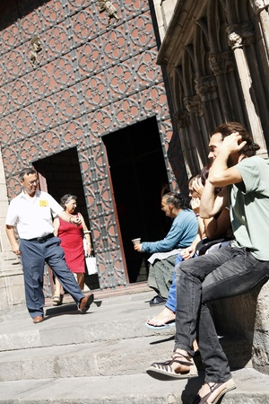 Barcelona,Spain - October 4, 2011: A gentleman donates some money a beggar woman which sitting in front of a church