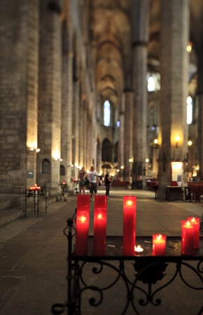 knave: Church candles in red chandeliers  Editorial