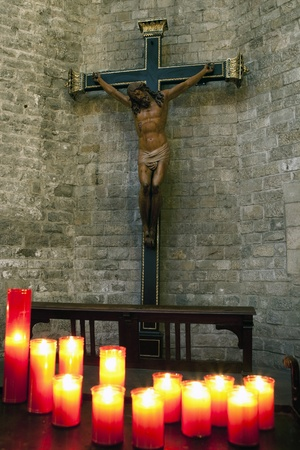 crucified: Jesus Christ on cross with candles in foreground