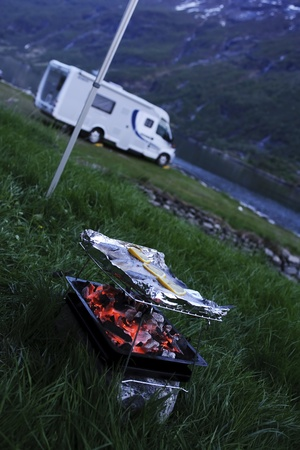 Outdoor lifestyle, glowing barbecue glowing in foreground of a parked campervan in mountainous terrain
