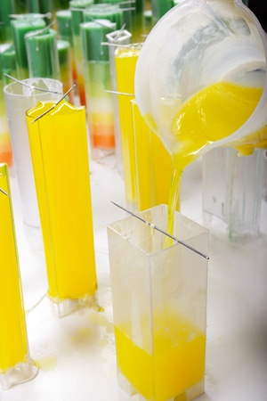 holiday maker: Candle manufacture , pouring colorful molten yellow wax into plastic moulds