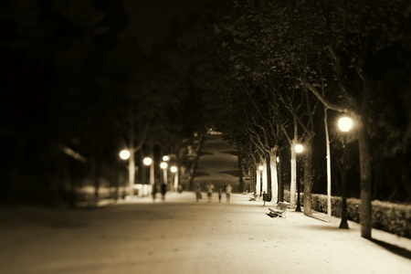 distant: Nightscene with an illuminated park bench and walkway with distant pedestrians Editorial