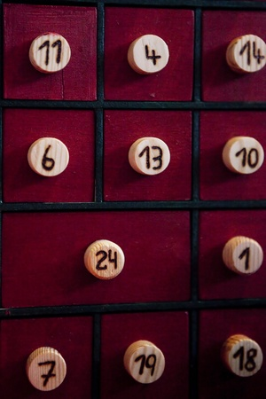 Handcrafted christmas calendar background with pine knobs on red pull, emphasis on 24th photo