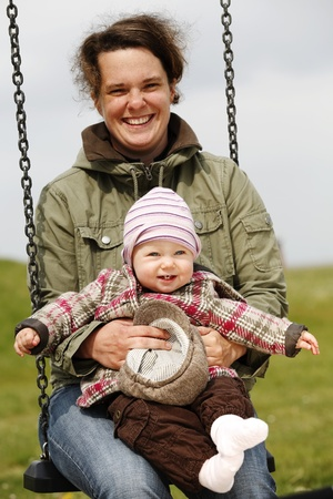 baby girl with her mom on a swing-shallow DOF photo