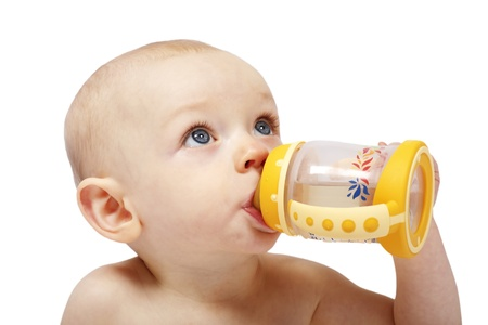 An adorbale little baby girl drinking from a colorful bottle with a teat