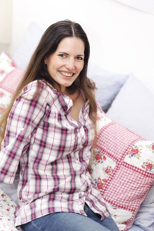 mature brunette: An attractive mature woman with big smile relaxing on colorful patchwork cushions