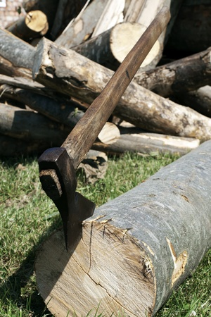 woodpile: A chopper is embedded in the end of a large log of winter firewood ready for splitting Stock Photo