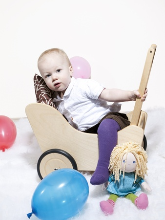 A cute young toddler climbs into a dolls pram while the doll sits alongside on the floor photo