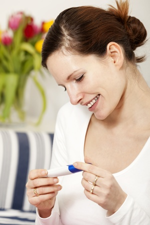Beautiful happy woman holding a positive pregnancy test kit in her hands and smiling