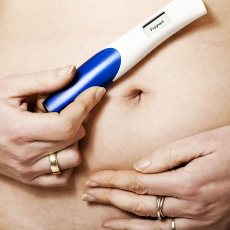 A womans hands holding a positive pregnancy test kit over her bare belly photo