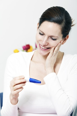 Beautiful happy woman holding a positive pregnancy test kit in her hands and smiling photo