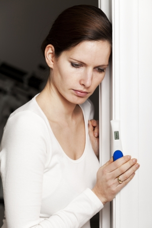 prueba de embarazo: Mujer triste con la prueba de embarazo negativa