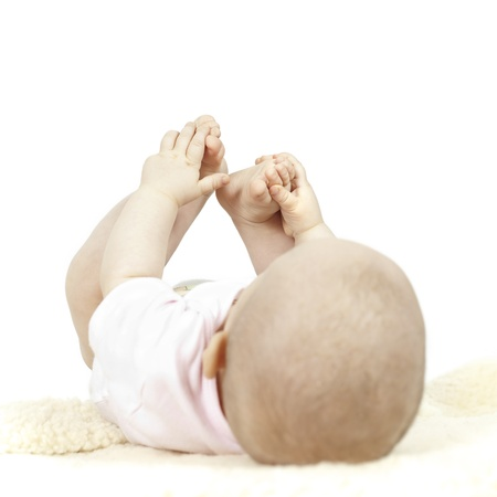 Young baby playing with her toes