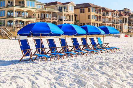 Blue umbrellas and lounge chairs on a white sandy beach in Florida
