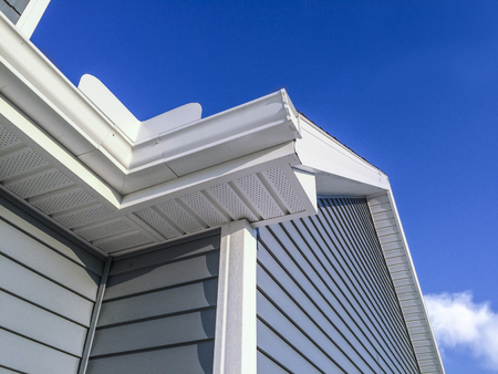 New white colored gutters, soffit, siding and facia on home. Blue sky in the background.