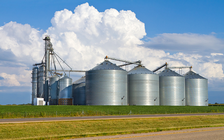 Large metal grain bins, used for storing grain, in a rural setting with blue sky and clouds in the background 版權商用圖片