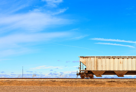 Single railroad car in a rural landscape with blue sky in the background