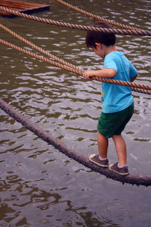 Boy crossing rope bridge at adventure playground photo