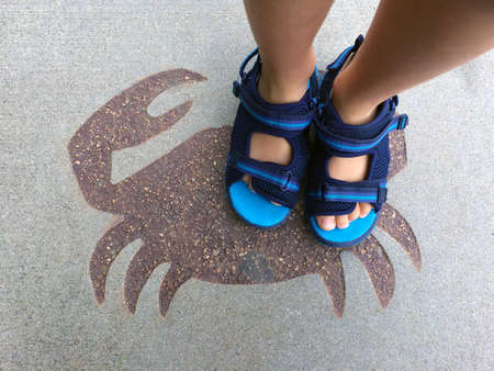 atop: A Young Childs feet atop a Crab Motif at the Local Swimming Pool