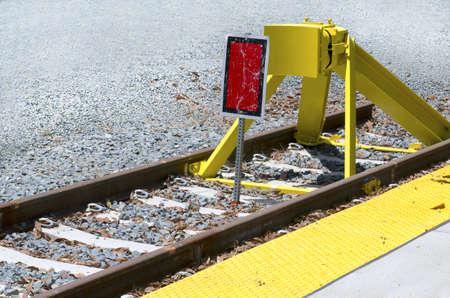 鉄道線路の行の終わりに赤いマーカー サインと黄色バリア 写真素材