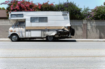 unsightly: An old and dilapidated recreational vehicle sits on a residential street.