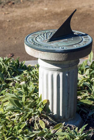 oxidized: An oxidized, copper sundial sits on a stone pedestal in the middle of a garden.
