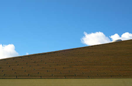 impregnable: An asphalt shingle roof on a single family home on a sunny day. Stock Photo