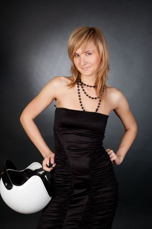 The beautiful, smiling blonde in a black dress with a motorcycle helmet. Black backgrounde. photo