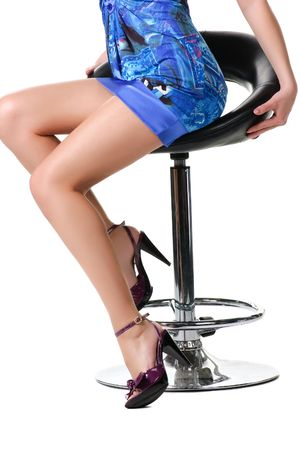Legs of a beautiful woman sitting on a chair. Isolated over white background . photo