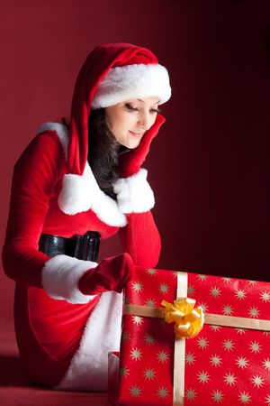 beautiful brunette in Christmas dress opens gift. on red. photo