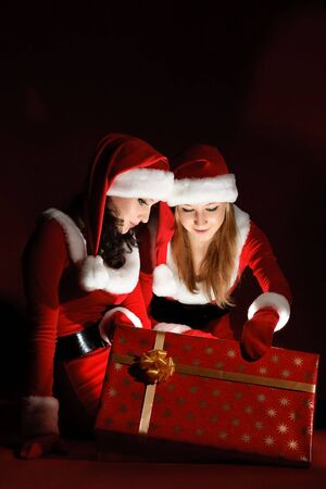 two woman in Santa costume opening christmas gift. on black  photo