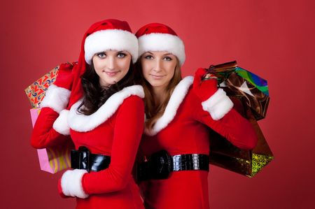 shoppingbag: Two women in dressed as Santa, with shopping bags . on red background .