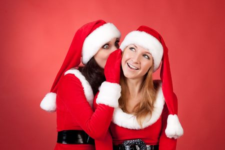 chatty: two happy young Santa girl talking over red background . Stock Photo