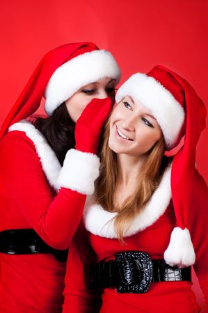 Two happy young Santa girl talking over red background . photo