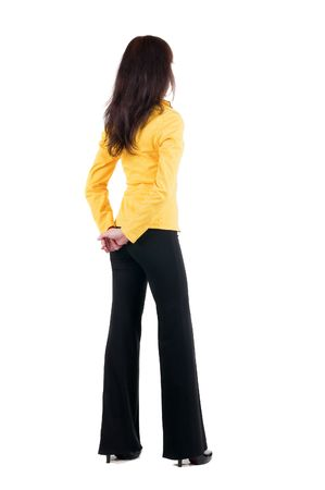 specifies: Young woman in yellow suit looking at wall. The rear view. Stock Photo