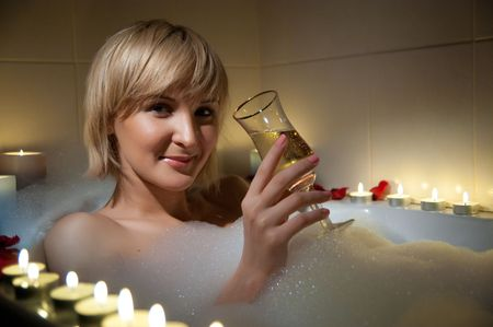 nude woman in foamy bath with petals of roses and by light of candles photo