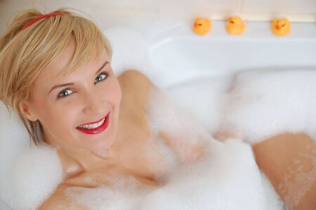 Smiling blond woman lying in bubble bath with toy duck photo