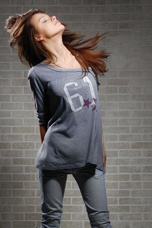 womanly brunette on brick wall background . Casual dress style  photo